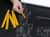 Jonge ambitieuze architect die de blauwdruk van een nieuwe hous voorstellen Stock Fotografie