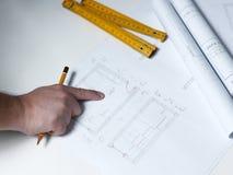 Jonge ambitieuze architect die de blauwdruk van een nieuwe hous voorstellen Stock Foto