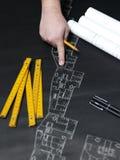 Jonge ambitieuze architect die de blauwdruk van een nieuwe hous voorstellen Stock Foto's