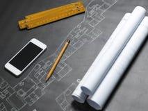 Jonge ambitieuze architect die de blauwdruk van een nieuwe hous voorstellen Stock Afbeelding