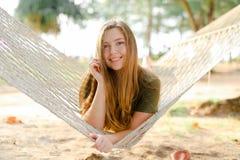 Jonge Amerikaanse vrouw die op witte rieten hangmat liggen en kaki kleding dragen Stock Afbeelding