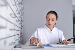 Jonge apothekervrouw die geneeskunde zoeken stock foto's