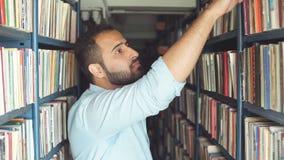 Jonge Arabische gebaarde mannelijke student die boek tussen planken in de bibliotheek kiezen stock videobeelden