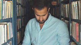 Jonge Arabische gebaarde mannelijke student die boek tussen planken in de bibliotheek kiezen stock footage