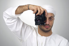 Jonge Arabische mens die houdend zijn reprografeerbaar om te schieten, geïsoleerd gebruiken Stock Afbeelding