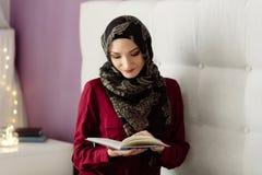 Jonge Arabische vrouw die in hijab een boek lezen royalty-vrije stock fotografie