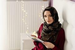 Jonge Arabische vrouw die in hijab een boek lezen stock fotografie