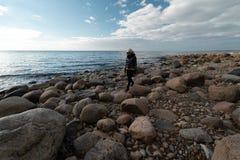 Jonge archeoloog op een keistrand die exotische rotsen op een kustlijn van een Oostzee zoeken stock foto