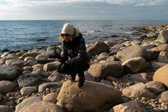 Jonge archeoloog op een keistrand die exotische rotsen op een kustlijn van een Oostzee zoeken stock foto's