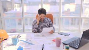 Jonge architect die met blauwdrukken in het bureau werken stock footage