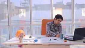 Jonge architect die met blauwdrukken in het bureau werken stock video