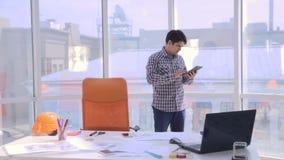 Jonge architect die met blauwdrukken in het bureau werken stock videobeelden
