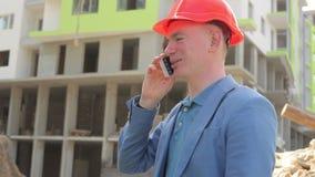 Jonge architect die op de telefoon bij de bouwwerf spreken stock video