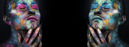 Jonge artistieke vrouw in zwarte verf en kleurrijk poeder Het gloeien donkere make-up Creatieve lichaamskunst op het thema van ru stock foto