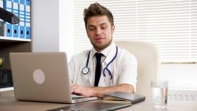 Jonge arts die aan de computer werken stock videobeelden