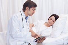 Jonge arts die aan patiënt spreekt Stock Foto's