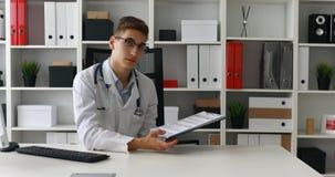 Jonge arts die document tonen en camera bekijken stock footage