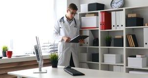 Jonge arts die documenten bekijken en camera bekijken stock videobeelden