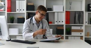 Jonge arts die documenten onderzoeken en bij camera glimlachen stock video