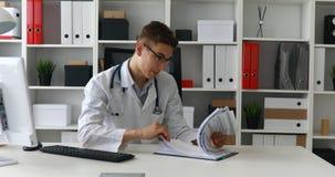 Jonge arts die documenten op het werk bekijken stock footage