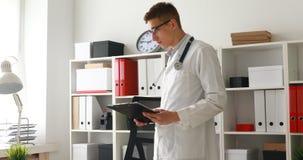 Jonge arts die documenten op het werk bekijken stock video