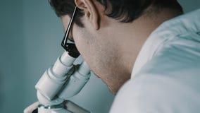 Jonge arts die door de microscoop kijken stock videobeelden