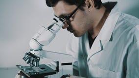 Jonge arts die door de microscoop kijken stock video