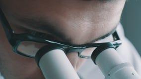 Jonge arts die door de microscoop kijken stock footage