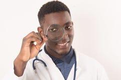 Jonge arts die in een vergrootglas kijken royalty-vrije stock afbeelding