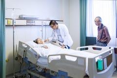 Jonge arts die hogere patiënt onderzoeken Royalty-vrije Stock Foto