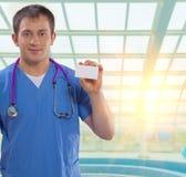 Jonge arts die kleine witte bezoekkaart tonen Royalty-vrije Stock Afbeelding