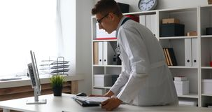 Jonge arts die met documenten bij computer op het werk werken stock footage