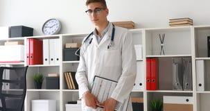 Jonge arts die met klembord in handen camera in werkplaats bekijken stock video