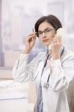 Jonge arts die telefoongesprek beantwoordt Stock Fotografie