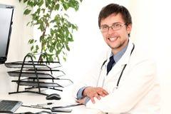 Jonge arts die in zijn bureau werkt Stock Foto