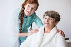 Jonge arts en bejaarde patiënt stock afbeelding