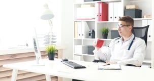 Jonge arts het drinken koffie in werkplaats stock videobeelden