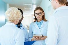 Jonge arts in laboratoriumlaag en glazen die notitieboekje houden en het werk bespreken stock foto