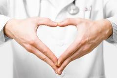 Jonge arts met hart gevormde handen. Royalty-vrije Stock Afbeelding
