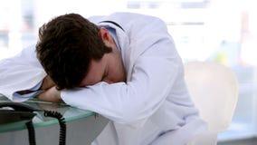 Jonge artsenslaap op een bureau stock video