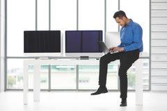 Jonge Asiabn-van de zakenmanzitting en holding nieuwe laptop computer royalty-vrije stock fotografie