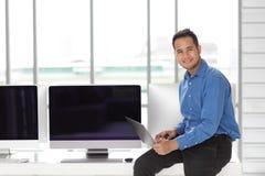 Jonge Asiabn-van de zakenmanzitting en holding nieuwe laptop computer stock foto