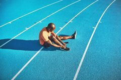 Jonge atleet die zijn schoenen verbinden vóór een looppas royalty-vrije stock afbeelding