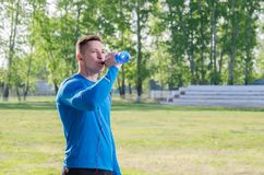 Jonge atleet in hoofdtelefoons drinkwater stock foto