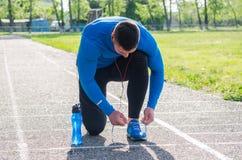 Jonge atleet in hoofdtelefoons, gebonden sportenschoenen royalty-vrije stock foto's
