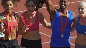 Jonge atleten hun goud en zilveren medailles tonen en koppen die bij toekenningsceremonie stock videobeelden