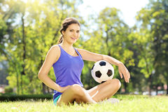 Jonge atleten vrouwelijke zitting op een gras en holding een voetbal i Royalty-vrije Stock Foto