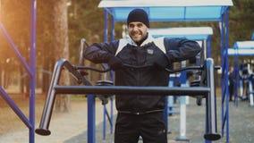 Jonge atletenmens die oefening doen bij openluchtgymnastiek in de winterpark stock foto's