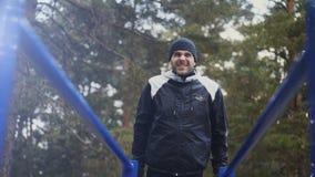 Jonge atletenmens die opdrukoefeningenoefening op bars in de winterpark in openlucht doen royalty-vrije stock foto's