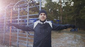 Jonge atletenmens die vóór training opleiding in de winterpark opwarmen Royalty-vrije Stock Afbeelding